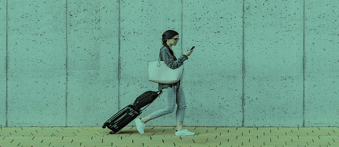 Woman walking with phone and suitcase