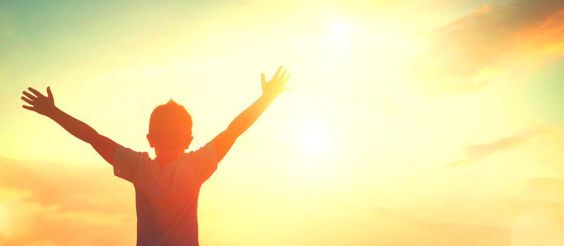 Boy with arms outstretched in the sunshine